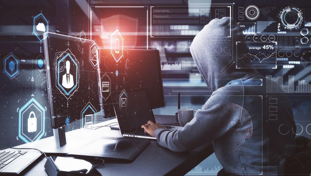 Person im Kapuzenpullover, die am Computer sitzt. Im Vordergrund Illustrationen zum Thema CyberCrime.