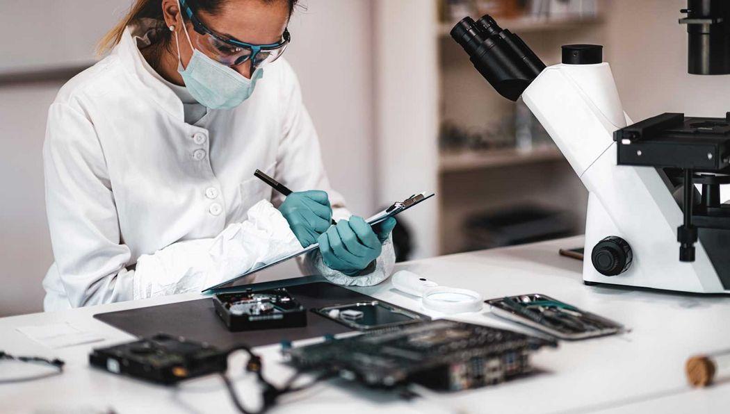 Eine Labormitarbeiterin untersucht Speichermedien