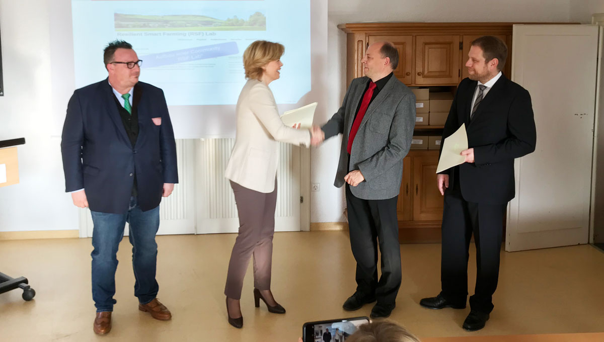 Julia Klöckner übergibt Dr. Ansgar Bernardi den Förderbescheid.