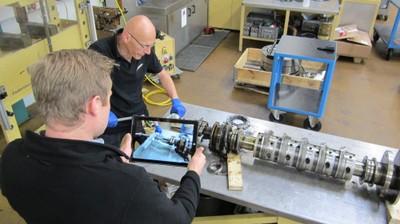 Zwei Werkstattmitarbeiter nehmen während einer Reparatur ein Lernvideo auf.