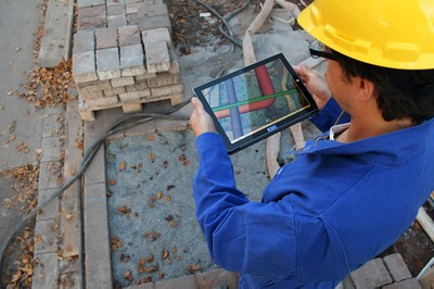 Bauarbeiter mit iPad, im Hintergrund eine Baustelle.